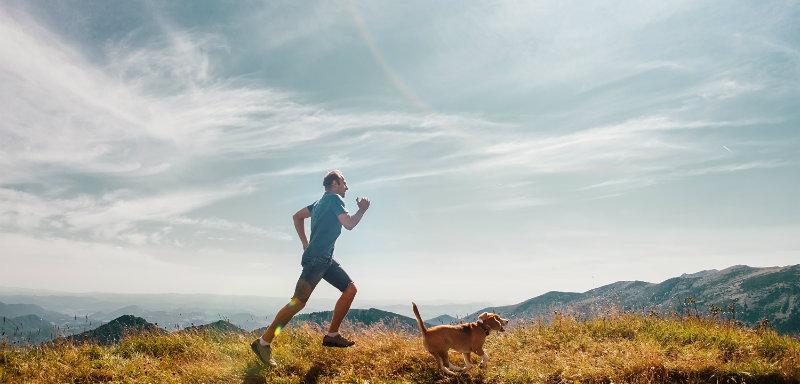 Un homme court avec son chien beagle au sommet d'une montagne pour lutter contre la dysfonction érectile